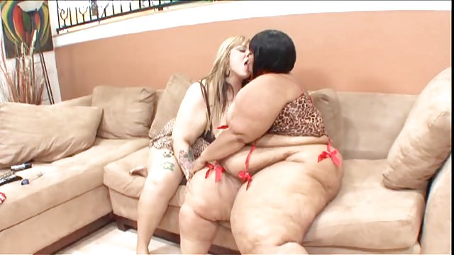 Busty black whores sit on the couch and play with their tight wet pussies